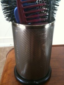 Old office pencil holder now holds combs and hairbrushes